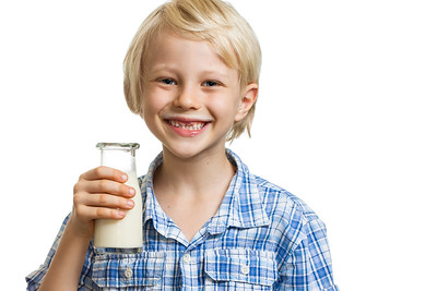 Happy boy holding bottle of milk.