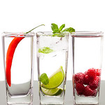 Three alcoholic beverages with fruits and berries