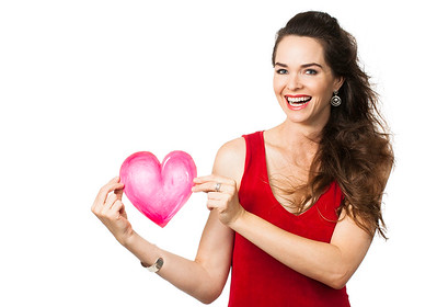 Beautiful laughing woman holding red love heart.