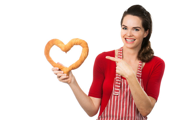 Beautiful woman pointing at a bread love heart.