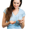 Woman in pain holding water and pill