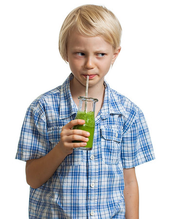 Suspicious boy drinking green smoothie