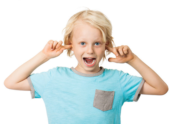A cute cheeky young boy smiling and sticking his fingers in his ears. Isolated over white.