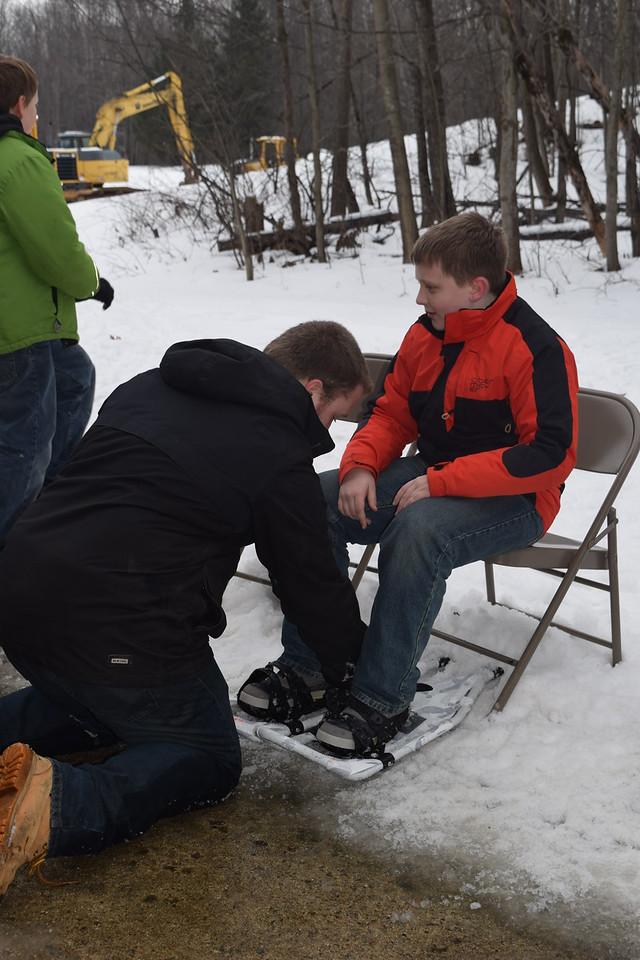 A Jay's Sporting Goods employee helps a boy put on showshoes for a hike through the woods at the MMCC Harrison campus.
