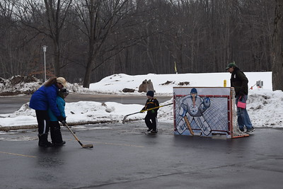 Parents help children learn how to hit hockey pucks at MMCC Harrison.