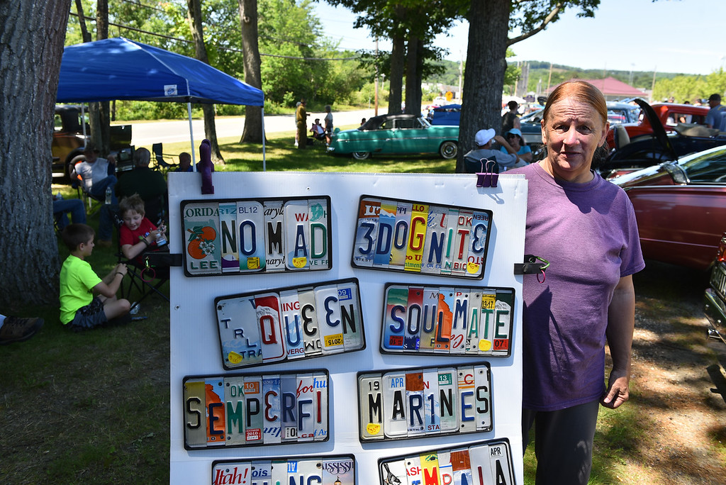 . Karen Jennings of Athol poses with a display of her custom license plate creations at Monty Tech in Westminster on Sunday for the Mid State Antique & Classic Auto Meet.  SENTINEL & ENTERPRISE JEFF PORTER