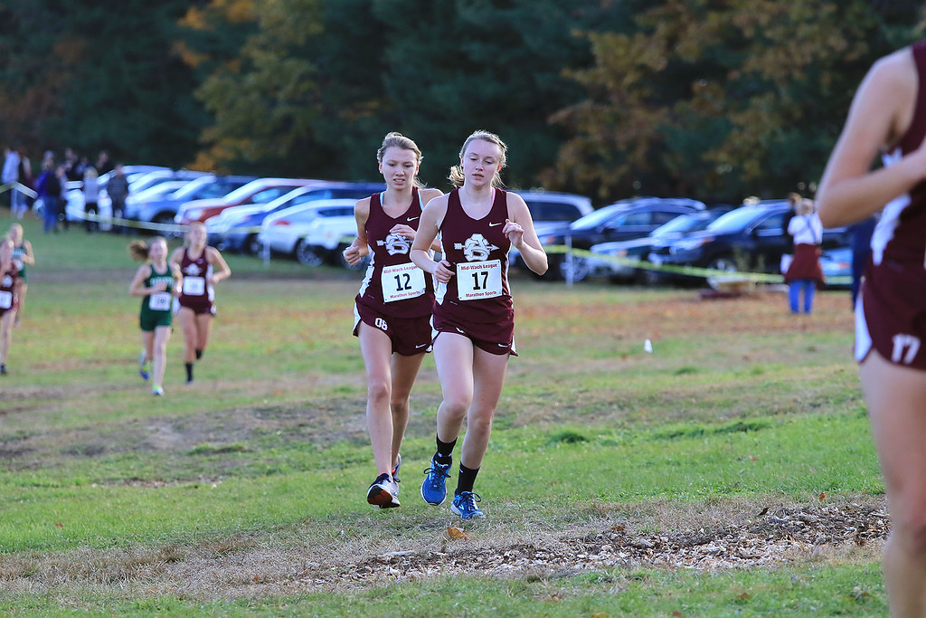 . Mid-Wach E girls cross country championships was held at Hollis Hills Farm in Fitchburg on Wednesday afternoon, October 31, 2018. Ayer Shirley Regional High School runners Katie Cadogan (12) and Mackenzie Marshall compete in the race. SENTINEL & ENTERPRISE/JOHN LOVE
