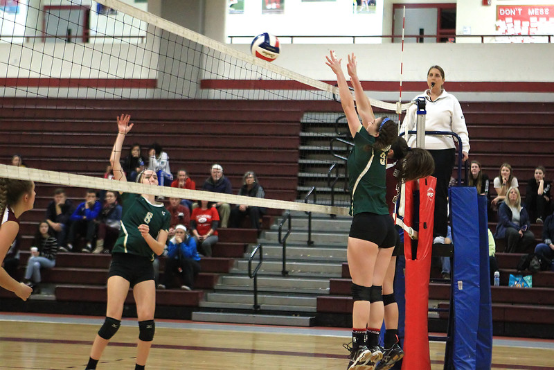 Jordan Bricknell of Nashoba hits the ball is Brynne McConnell (Nashoba) and Brecken Gingras (Groton-Dunstable) attempt block