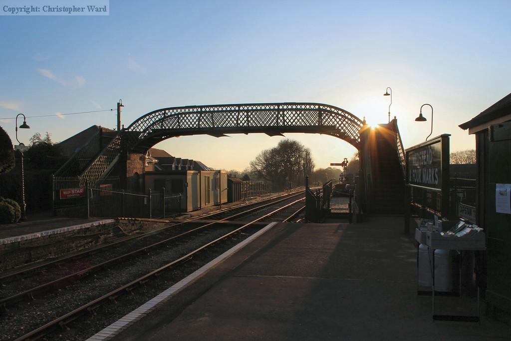 The sun starts to set behind the footbridge at Medstead