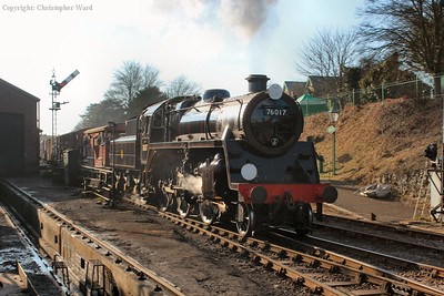 76017 catches the low sun as she canters through Ropley with the freight