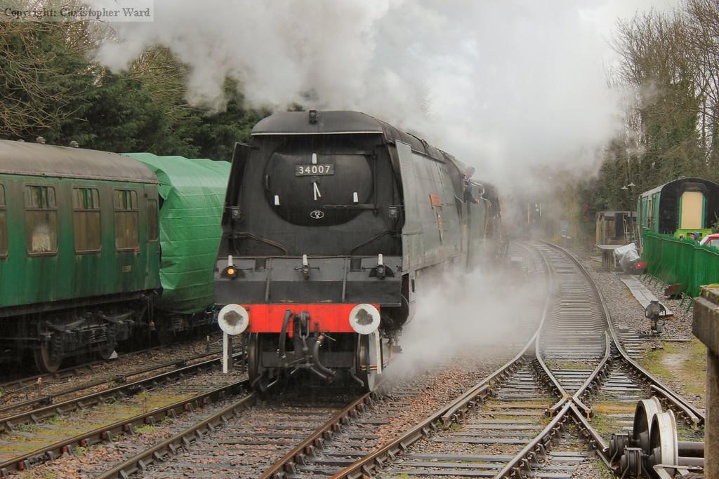 The rain teeming down as the Bulleid runs through the station