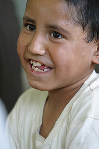 """Afghanistan (Panetta)  Ehsanullah Nasrullah, who is eight, thoroughly enjoyed attending school. In fact, he excelled so well that he was many grades ahead of the other children his age.  One morning Nasrullah and his cousin, Nabile, were running late for class. As they scurried to school, Nabile's attention was drawn to a small  yellow canister. Thinking it was one of the yellow cans of biscuits/rations that the US had dropped, he picked it up.  Without warning the can began to smoke. Unaware of its deadly contents, Nabile threw it into the air-in the direction of Nasrullah. The canister detonated, sending shrapnel in all directions, tearing flesh from the bodies of the two young boys. Nasrullah's wounds were nearly fatal; so severe, in fact, that doctors wanted to amputate his two legs as well as an arm.  When asked what his life was like before the explosion, he promptly and assertively responded """"Perfect!"""" But all has changed for Nasrullah and his family. They struggle to pay the exorbitant cost of his ongoing care. Nasrullah describes the pain comparable to loud bells ringing in his head. With some scars visible on his face, it seemed plausible that the pain is due in part to the shrapnel from the bomblet, but one glance into the eyes of this inspiring little boy and his mental afflictions are clearly dramatized. When asked what he wants to be when he grows up, his face lights up as he responds: """"The President! ... so I can bring peace to my country."""""""