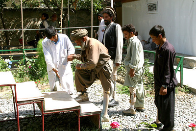 Afghanistan (Panetta)  ICRC, Kabul (Afghan Red Crescent). Learning how to walk with new prosthetic limbs.  The vast majority of the staff and patients are amputees, some double amputees. As we walked through the facility we passed by several patients who, one by one they would, almost methodically, lift their pant leg to show their prosthetic, or they would remove their prosthetic to show reveal their limb. And although this was generally followed by a handshake or an arm-shake for those without hands, it was always followed by what I perceived to be a look of gratitude. And although there was little we had to offer, the gift we were able to give was our presence; it was simply the gift of our time, and our ability to look into their eyes and affirm their courage.