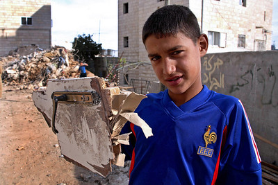 Bethlehem, Palestine 2006 (Panetta)  A young boys hold the remains of the front door of a home that was demolished by Israeli forces.   When family and friends began throwing rocks at the bulldozer Israeli soldiers opened fired killing a teenager and leaving an elderly woman brain dead after a bullet struck her in the head.