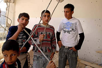 Bethlehem, Palestine 2006 (Panetta)  Young boys stand in a house that was demolished by Israeli forces just an hour earlier.  The walls are riddled with bullets holes from Israeli military sniper fire that killed 2 Palestinian youth.