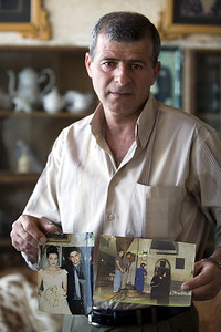 """Johnny Yousef Thaljiyye, 17, as shown in the photos held by his father died (October 20, 2001) during the seige / shelling of Bethlehem. Known as the """"Martyr of the Church of the Nativity""""  Johnny had just left Mass and was playing with his 4-year-old cousin in Manger Square when he was killed by an Israeli sniper. Palestine / Israel (Panetta)"""