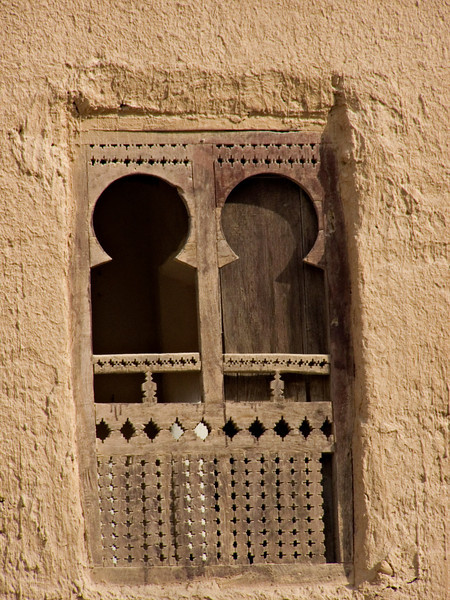 """Window, Tarim.  Tarim lies to the east of the regional capital of Sayoun, which I flew to on arriving in Yemen.  Tarim is an old town with strong religious significance, so when I visited on a Friday there was not much activity in the streets.  The shared taxi that took me to Tarim was full of young men reciting from the Koran, on their way to attend Friday prayers in Tarim.  Halfway through the trip one of these pious young men closed his Koran, turned to me and said: """"Today Friday.""""  I affirmed the truth of the statement, and prepared for a religious discussion.  The next words out of his smiling mouth were """"Seven o'clock, Germany-Costa Rica!""""  This was to be the first match of the 2006 World Cup, and the young man's gleeful anticipation was a fine way to dissolve any preconceptions on my first full day in Yemen."""