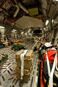 C-17 cargo hold looking front to back, all passengers sit on the wall seats.