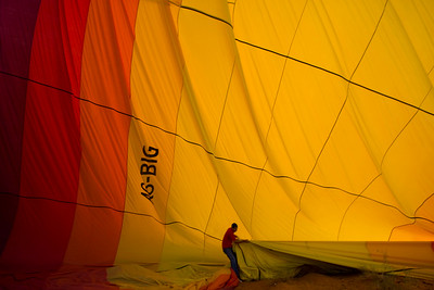 A worker tries to gather up the big balloon as it deflates.