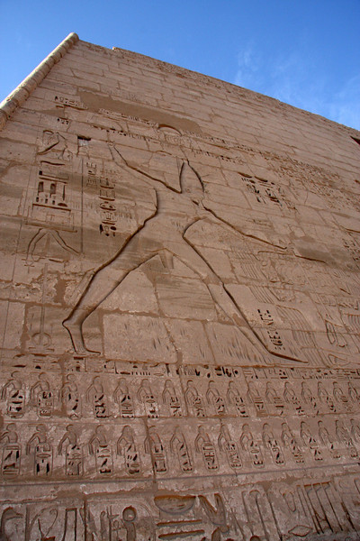Ramses III battling Libyans on the First Pylon - the size is 5 times larger than life 2007, The Temple at Medinat Habu is located on the West Bank of the Nile in the ancient city of Thebes, now called Luxor. It's not as large as Karnak Temple, but the colors are better preserved and there are far fewer tourists. It's located next to the sleepy farming village of Kom Lolah. Some travel books name this site as the most overlooked in Luxor