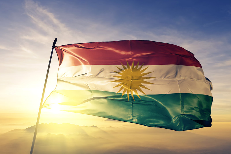 Kurdistan flag textile cloth fabric waving on the top sunrise mist fog