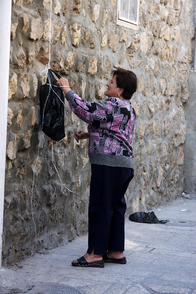 shopkeeper tieing a bad of goods to a lift rope upto an apartment above. Jerusalem, The Old Walled City, 2007
