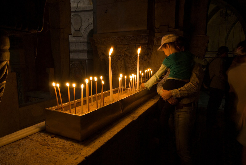 Father and daughter lighting candles in The Church of the Holy Sepulchre - Jerusalem