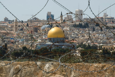 Dome of the Rock and skyline seen behind barbed wire - Jerusalem, Israel