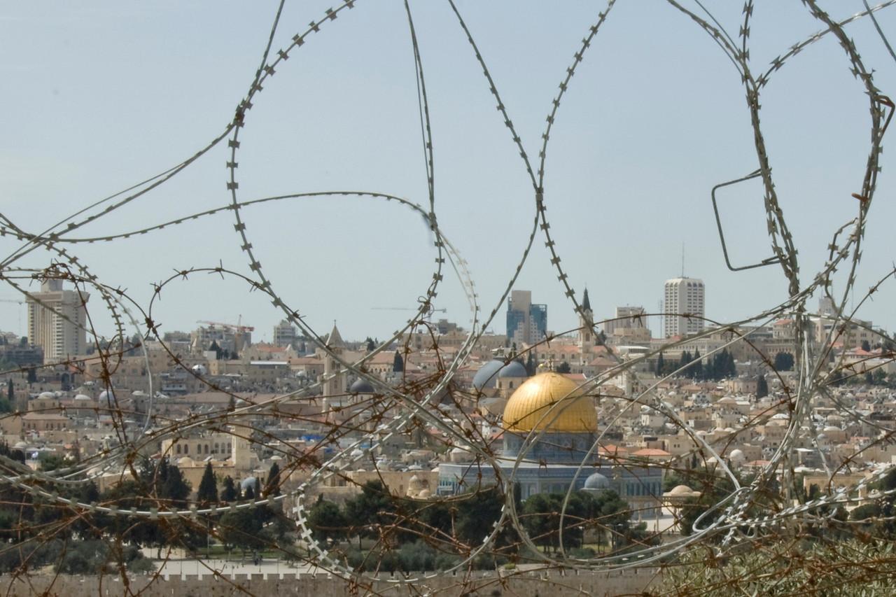 Jerusalem skyline as seen behind barbed wire - Israel