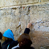 Pressing a folded prayer into the cracks of the Wall