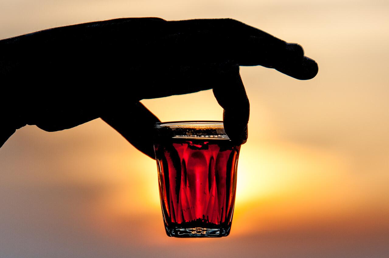 Bedouin tea in a shot glass during sunset in Feynan, Arabah, Jordan