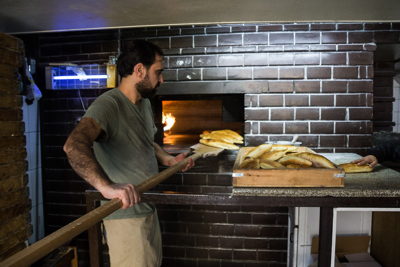 Removing Freshly Baked Bread from the Oven at Saladin Bakery (©simon@myeclecticimages.com)