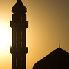 A mosque silhouetted against the sun. Speakers positioned on the tall minerat are so EVERYONE can hear prayers during the day and night.