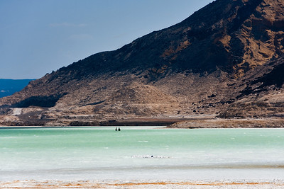 A bed of razor sharp salt crystals under your feet instead of sand don't keep the curious from walking in the shallows of Lake Assal.