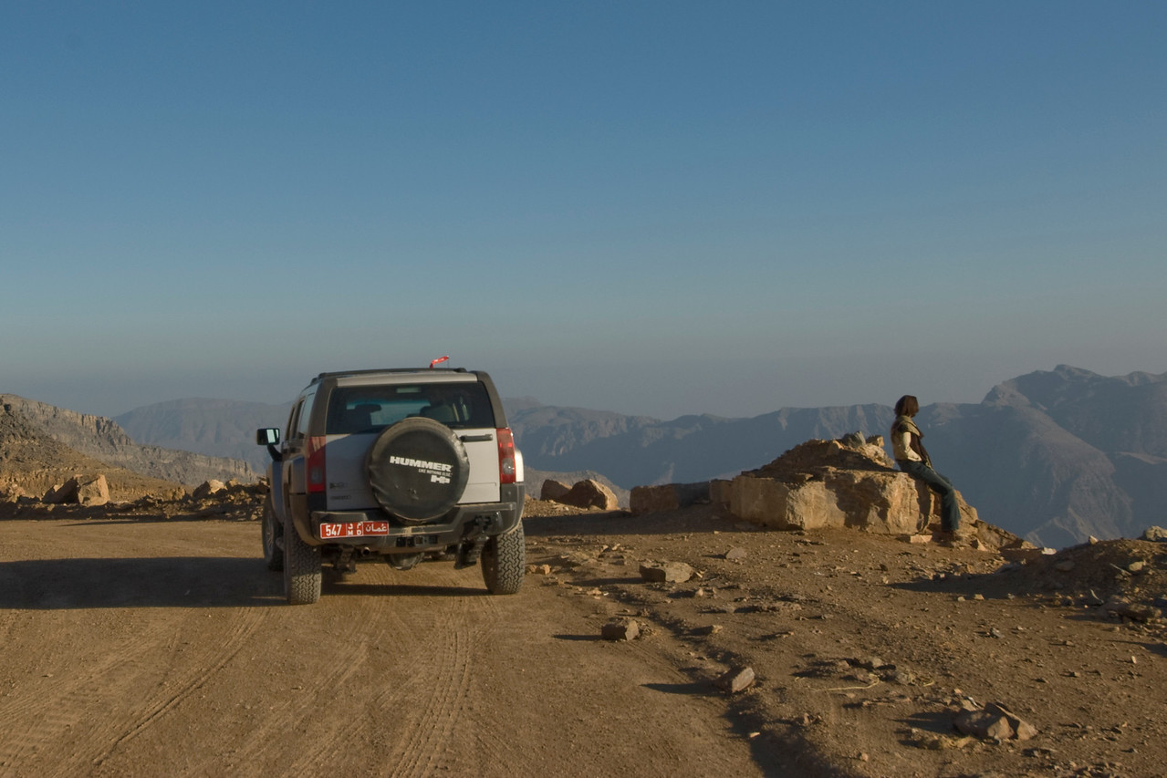 Woman and Car overlooking Mountains - Musandam, Oman