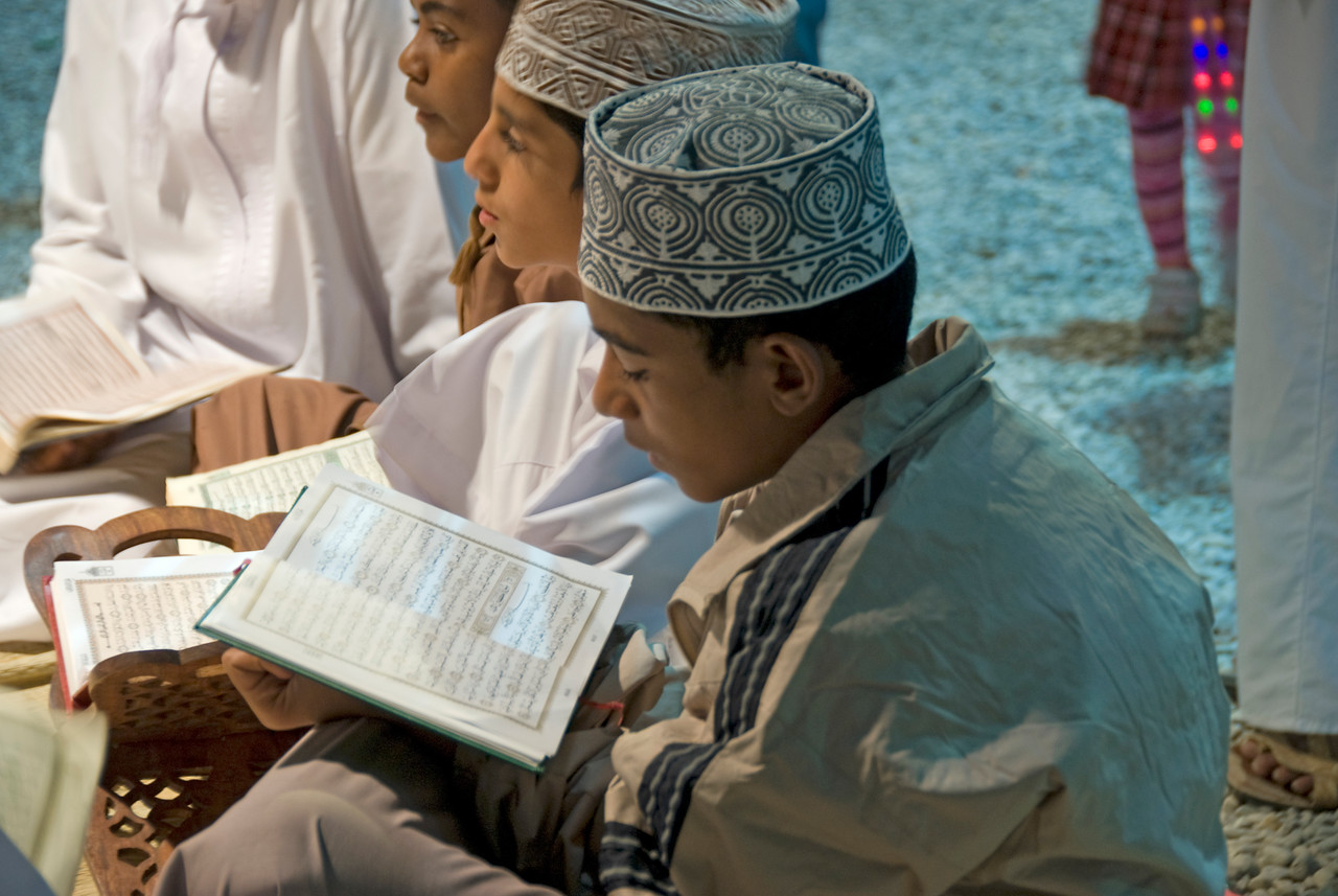 Boy reading the Koran in Muscat, Oman