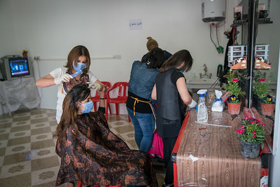 Shekhan,Nineveh, Iraq. March 2017. A beneficary of IRC / UNwomen program that gives up to 1000 USD small business start up grants after a 9 day small business training program in which applicants must succefully form a business plan.  She used her grant money to start up a hairdressing salon.   Full transcripts  13:38 So, shall I talk about how things were before we arrived in Shekhan? 13:45 Yes, briefly. 13:47 When we first came here, things were bad for us. 13:49 I didn't have the means to open a shop. 13:50 I had a beauty salon in Bashiqa. 13:53 A big one. 13:54 But here, I wasn't able to open one because we didn't have the means to do that. 13:59 I worked from home, but not many customers would come over. 14:02 Some customers came to me but for instance, brides didn't. 14:05 Some girls came to get their hair done for parties, but not brides because their families wouldn't accept to send them to me. 14:12 When I met Mr. Niwar,.. I registered with the organization. 14:18 He offered me help, so I asked if he could help me open a salon. 14:24 I mean it is a once in a lifetime project, and I love my work. 14:29 I registered with the organization and I succeeded in getting a grant. 14:34 I spent all the money on my project because it is my dream. 14:40 I would like to further develop my dream. 14:43 I want to improve my salon even more. 14:44 If not in Shekhan now, then in Bashiqa. 14:49 My teacher, the one who taught me hairdressing, went to Germany, we agreed to open a big salon or a compound even, when she gets back. 14:57 It will be for accessories, hairdressing, nails, and everything. 15:03 This is our joint dream. 15:05 We will do that together and we will open the salon when we go back to Bashiqa. 15:15 My experience with the course… 15:18 before I took it, I didn't know anything about accounting, or how to organize the business. 15:22 They taught me all those things, and how to calculate my profit or losses so that no one takes advantage of me. 15:33 Excuse me. 15:34 So this has helped me a great deal. 15:37 So now whenever I perform a job or hire someone to maintain the shop, I keep notes of everything, of what I made or what I spent. 15:49 Also, I learned how to save money. 15:51 Thank God, it has been a blessing from God. 15:54 I get customers and I get bride customers too. 15:57 Today I haven't had any customers because I had made room for this interview in my schedule. 16:04 With the help of the committee, I have learned things I hadn't known about before and now I make more profit. 16:33 No, at the beginning I never felt safe. After we left, I didn't feel safe. 16:36 When Bashiqa was liberated we felt safer. 16:40 We felt safe enough to come and go as we pleased. 17:07 It was good and bad. 17:10 Everyone in Bashiqa, Barzan, and Sinjar had money but didn't spend any of it. 17:17 We didn't have money. 17:20 My husband would work or I would work a little and we got by. 17:25 But gradually we got used to the place and the people, and now they can't imagine their lives without us. 17:31 At the beginning when we didn't know each other things were very difficult, but now things are different. 17:35 We got better acquainted. 17:40 Yes, and now people tell us they would like to come visit Bashiqa. 17:42 It was very difficult at the beginning. 18:19 I told my husband I won't go back to Bashiqa until I have established my business fully because work here is better. 18:27 Because things are bad in Bashiqa. 18:30 I have customers now from many areas, such as …, Mahad, Alqosh, and other places. 18:39 They have become regulars and they come and visit me. 18:42 I will not leave this place before I establish myself well. 18:46 I wish to make my dream come true before I go back to Bashiqa. 18:58 Yes, of course. 19:02 At first, they didn't know me and didn't know my work but gradually they started to know more about me with each visit. 19:08 A reputation started to form about me as people started to tell each other about the quality of my work. 19:14 There is another beauty salon here called Berivan Salon, but unfortunately the woman there doesn't do a great job. 19:19 She doesn't use advanced techniques, unlike in Bashiqa and Barzani where hairdressers used to develop their skills continuously and they used to learn new hair and makeup styles to attract customers. 19:31 Also you should be able to accommodate what the customer wants. 19:32 They usually have an opinion and I also tell them my opinion, and this helps develop my work. 19:39 I also have hair and makeup videos to make sure that the customer sees my work. 19:43 So, if she doesn't get to see my work directly, she can watch a video on her mobile phone so that she knows what I have available in my salon. 20:06 Some girls come to me to be trained here. 20:11 So, the hairstylist usually takes money to train them and give them a training course. 20:17 So a girl would have a 3-month course at 150, so they charge 50 per month. 20:25 But I felt like I needed to help these girls just as the committee had helped me, and my friend had helped me free of charge. 20:32 So, I decided not to charge them for the training because they help me and I help them. 20:35 So I teach them my trade until they get better, so they don't really have a long time left to spend here. 20:43 So when everyone goes back home to Bashiqa they would be ready to work, and they already know everything including straightening and dying hair and all that. 20:52 These are my special helpers. 20:54 So when I need them, they come to help me. 20:59 A week ago we had a job at 12 AM and we worked until 8 AM. 21:05 So the work is hard and requires that they stay with me sometimes for long hours. 21:08 Thank God, they are good girls, and they know everything by now. 21:11 This friend of mine who helps me with hairstyling; she is a hairstylist. 21:17 Sometimes I ask her to come and help me. 21:20 She has her own shop but it's not doing very well, so I wanted to help her out. 21:26 And the girls are good too. 21:39 In the end I would like to thank the organization for its help. 21:53 Of course. 21:53 The most important thing is to help others. 21:58 So had it not been for the organization, I wouldn't have found a job. 22:02 I would have stayed at home working only a little. 22:06 Had it not been for the organization I wouldn't have had this better job. 22:08 So thank God I found work through the organization. 22:11 Thank God. 22:13 If one wants to live life fully, she should work to fulfil her dreams, and I wish to keep improving. 22:18 I have the ambition to surpass my current success. 22:21 I thank the organization so much, and especially … 22:28 Had they not worked to support poor people we wouldn't have achieved what we did. 22:33 Some poor women who come to help me ask me why I haven't told them about the organization, because they also would like to work. 22:40 The organization still searches for new projects but not at the moment. 22:44 … in Bashiqa. 22:51 But the ARC organization is the best. 22:54 All the girls are happy with it because they help the poor. 22:57 Without the organization no one would have been successful. 23:03 So I extend my most sincere thanks to them. 23:06 I don't know how to express how grateful I am for their help.