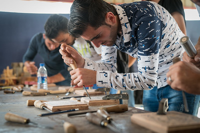 Young people in Za'atari take part in a woodcarving workshop with Turquoise Mountain as part of UNICEF X ONE Start Up Za'atari event