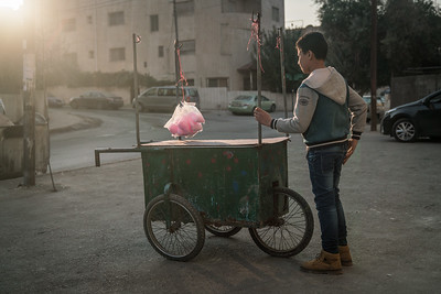 Young Syrian refugee living in Amman forced to  sell cotton candy on the street to provide for his family instead of attending school.