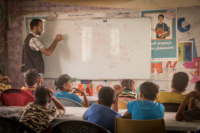 "Inside  math class at Save the Children - UNICEF drop in center in Za'atari Refugee camp.   Mesh'al, (yellow shirt) is a Syrian refugee from Hrak City,16 years old and living in Za'atari Camp in Jordan.  Like many boys in Za'atari he has not gone to school since moving here and work transporting people's groceries across the massive camp home to over 80,000 refugees.  He visits a drop in school operated in partnership with UNICEF and Save the Children where he learns Arabic, math and hair dressing.   ""I was in the 7th grade back in Syria and bombing happened and other stuff. We came to Jordan. I must be in the 10th grade now but I didn't study, I worked on a wheelbarrow to support my family.  If I go to school there will be no one to support them. The work is exhausting.  When I was little I loved to read. and wanted to become a teacher.   But now if I want to go to school I will go back to 5th or 6th grade. I became old now Its not going to work.  In my free time I go to the child's club. I am learning hairdressing. I love hairdressing cause its good and beautiful and you won't make your clothes dirty. To me hairdressing is a profession, it will remain for my future. But mathematics and arabic will remain mine. If I learn them, they will remain mine. Inshallah, I am planning to become successful Tomorrow in the future I will open up a shop and I will have this profession. "" - Mesh'al  In Jordan, of the estimated 220,000 school-aged Syrian refugee children  registered by UNHCR, only 130,000 enrolled in the public school system in  camps and host communities. While 30,000 children attended various forms of informal education, leaving approximately 60,000 not accessing any form of learning."