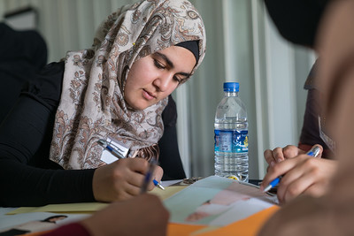 Fatima, 18, taking part in a fashion design workshop in Za'atari Refugee Camp, at Start-Up Za'atari, an event hosted by UNICEF and The One Foundation. Her group designed a dress, incorporating a cape with feathers to represent freedom and women's empowerment.