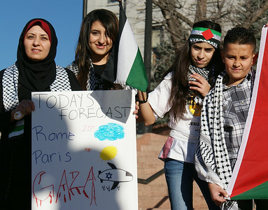 Woman wearing hijab holding sign about Gaza, next to her young girls and boy with Palestinian flags.