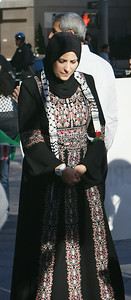 Woman wearing hijab and tradition dress, hands folded, looking down.