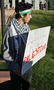 Young man wearing keffiyeh and Palestinian flag headband, holding sign.