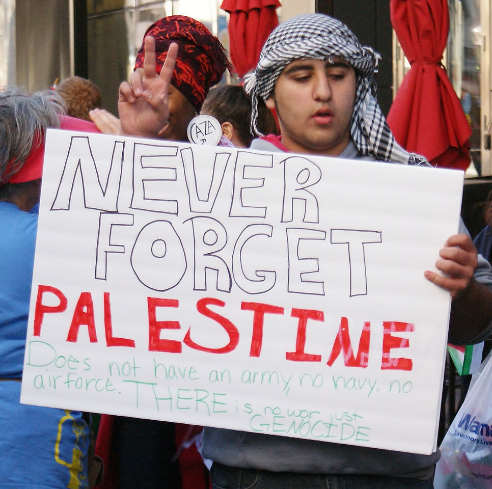 Young man wearing keffiyeh on head, carries sign about Palestine and raises hand in peace sign.
