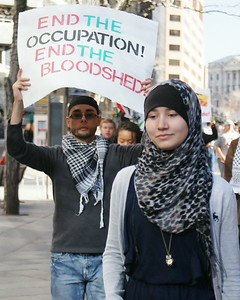 Young woman wearing hijab, behind her, protester raises sign about occupation of Palestine.