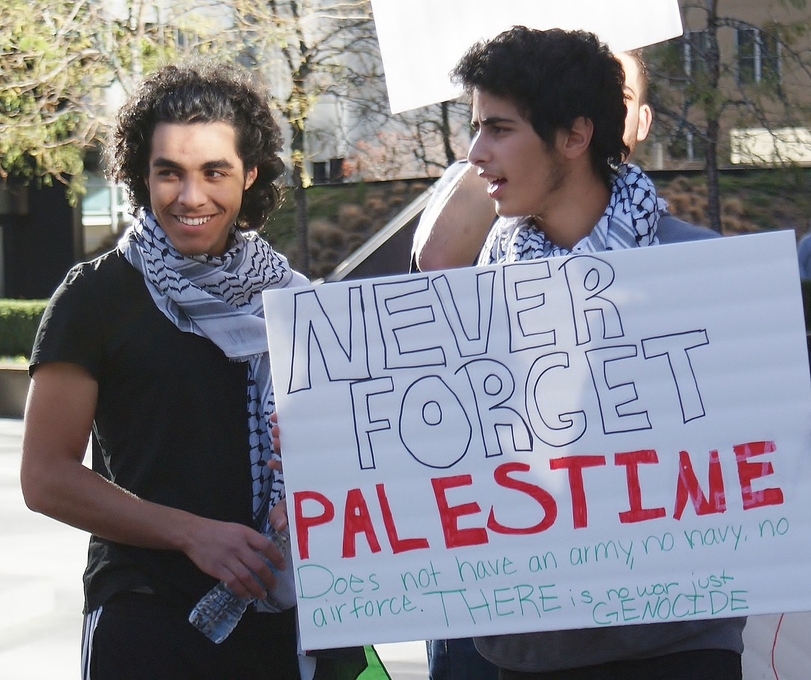 Two young men wearing keffiyehs, one smiling, other holds sign about Palestine.