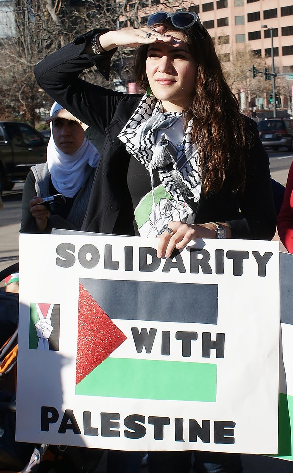 Young woman holding sign about Palestine, raises hand to shield eyes from sun.