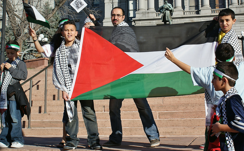 Father and young boys display Palestinian flag