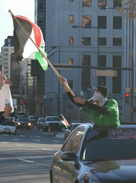 Young man wearing kiffeyeh over face, stading up out of moving car sunroof, raising palestinian flag.